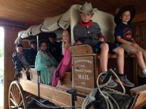 Local students riding a stagecoach through History