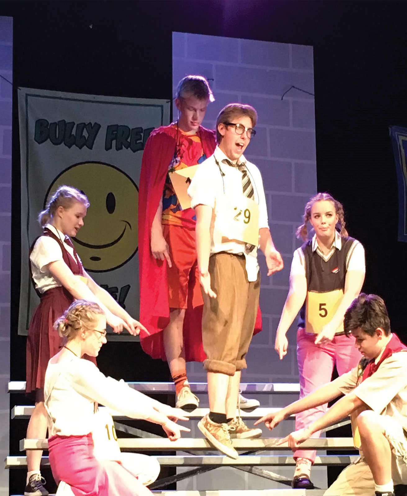 Senior Bowen Gray as William Barfee (center), freshmen Maddie Ruttenberg as Olive Ostrovesky and Cate Kauber as Marcy Park, sophomores Henry Kacik as Leaf Coneybear, and Emma Belew-LaDue as Logainne Schwartzandgrubenierre, and freshman AJ Knorr as Chip Tolentino.