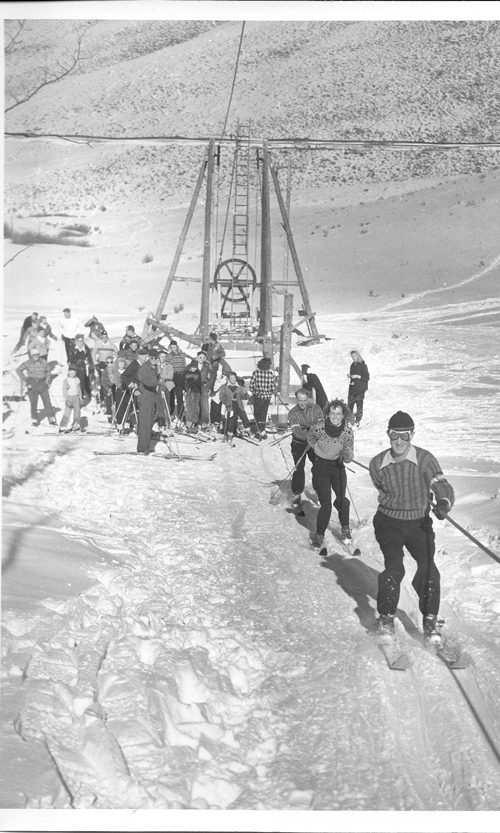 Caption: Barney McLean is in front and Gordy Wren is third in line on the rope tow at Snow King Valley at Hot Sulphur Springs. They are both wearing their Olympic sweaters.